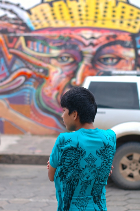 A young Bolivian kid, waiting for a cab in front of some pretty cool graffiti.